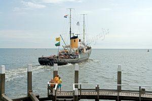 Sleepboot vaart de haven van Oudeschild uit